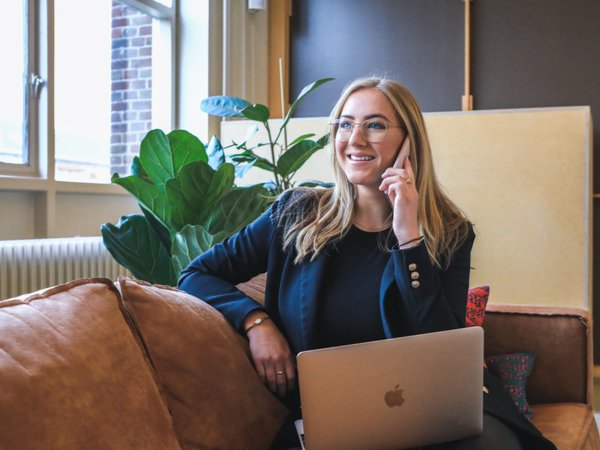 Woman smiling and on the phone with a laptop on her lap