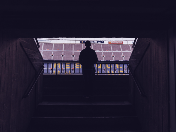 Silhouette of a person looking out into football stadium
