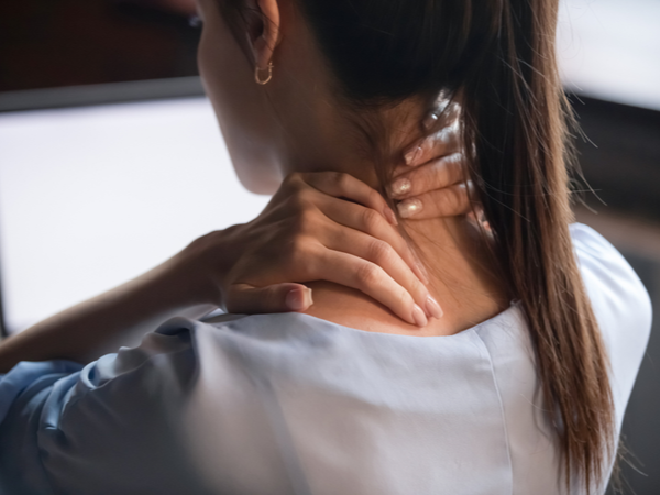 Woman rubbing her neck at her desk