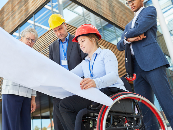 Woman in a wheelchair showing blueprints to colleagues