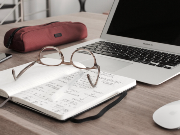 Laptop, glasses, notebook and pencil case on a desk