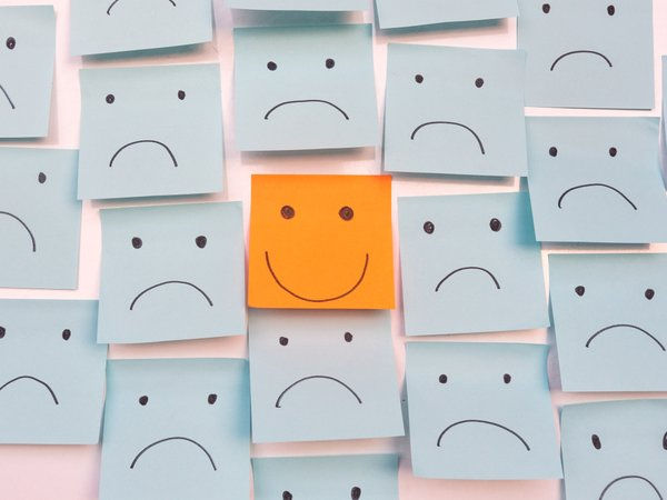 Yellow post-it note with smiley face, surrounded by blue post-its with sad facese