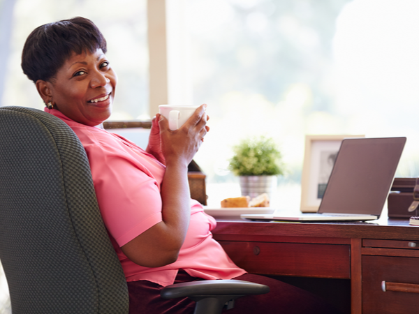 Middle-aged woman holding a hot drink by her desk