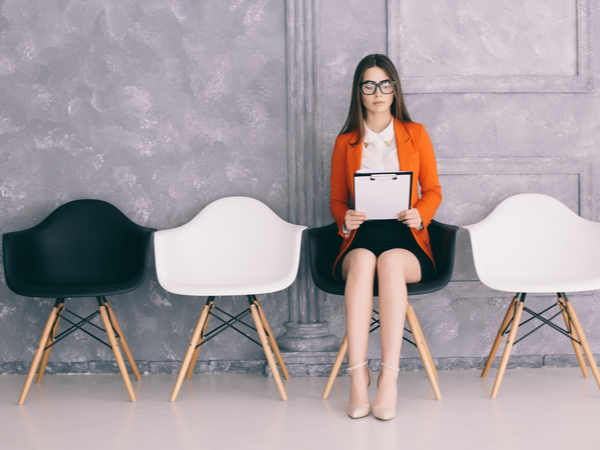 Young woman sitting on a chair in a waiting room before an interview