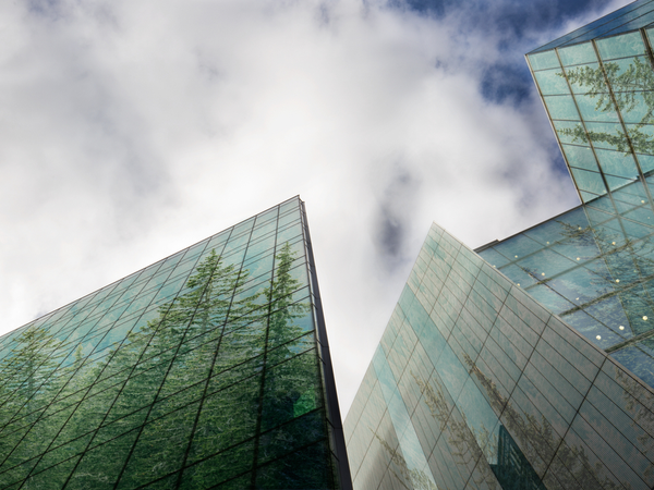 Looking up at tall glass buildings with trees in the reflections