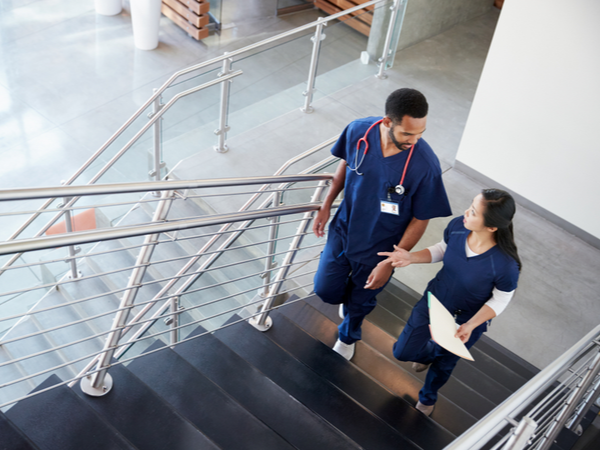 Two healthcare professionals talking as they walk up the stairs