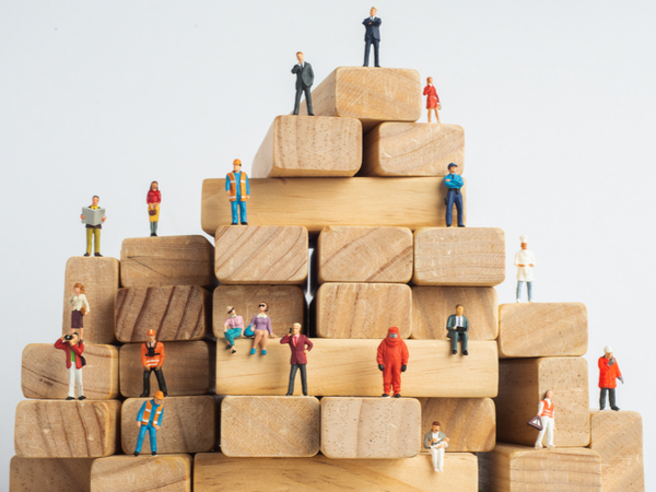 A tower of wooden playing blocks with small human figurines on them