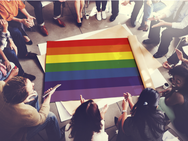 A group of people in a discussion around a Pride flag on the floor