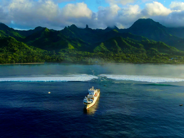 A ship sailing towards one of the Pacific Islands