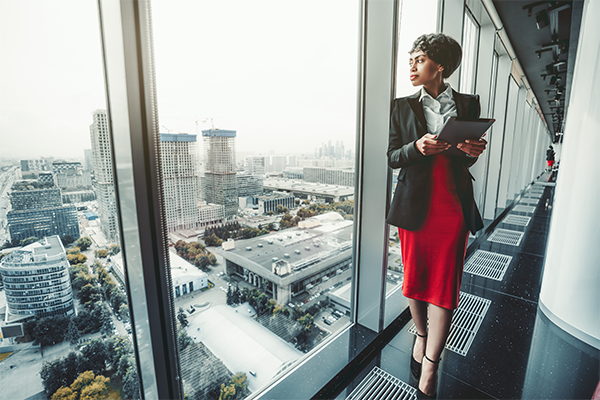 Business Woman holding ipad stood at full length window looking out at business scape