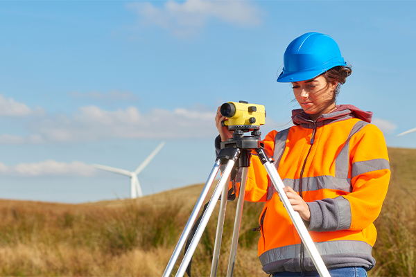 Women in high vision vest and hard helmet using equipment to scan the landscape, wind turbine in background