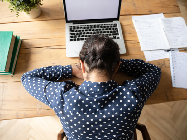 Woman lying down with her head on her desk