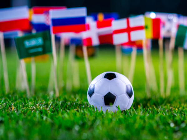 A toy football in front of minitature flags of different countries