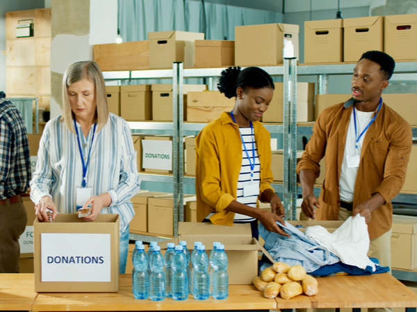 People working in a warehouse putting food and clothing donations in to boxes