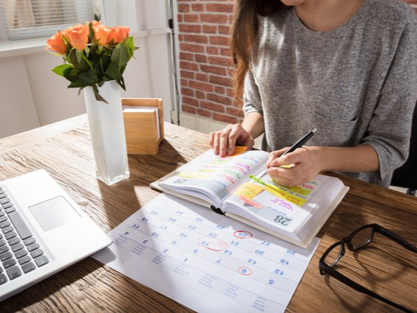 Person writing in a personal planner, looking at a calendar