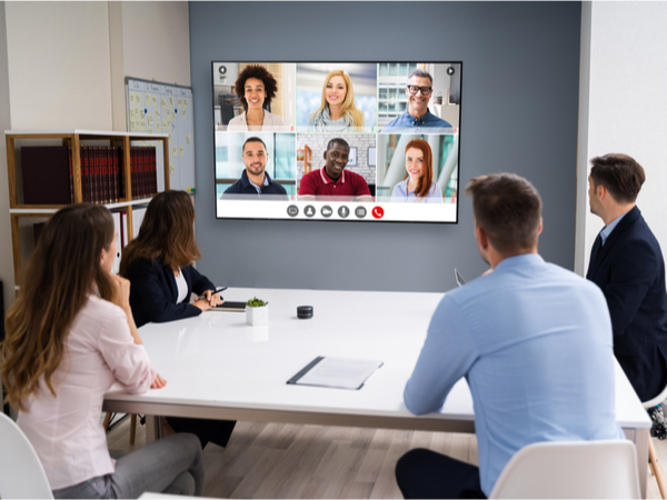 A group of business people sat in a meeting room talking to colleagues on a screen in front of them