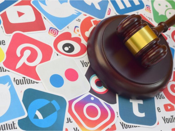 A gavel on a background of social media logos