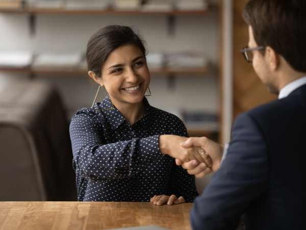Young grad shaking hands to accept job offer