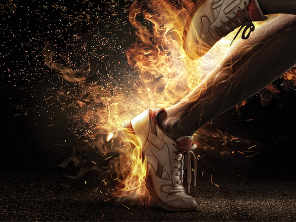 A sprinter wearing trainers with flames coming out of them