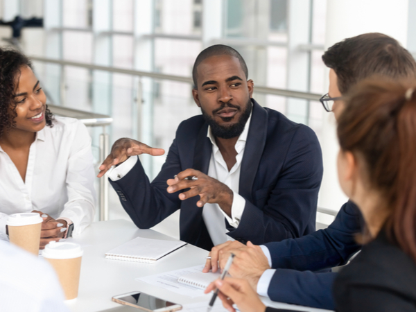 Man in suit explaining something to a group of businesspeople
