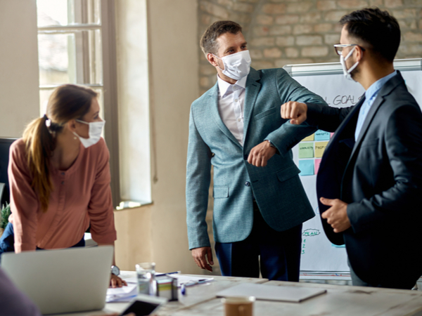 Business coworkers elbow bumping while wearing protective face masks