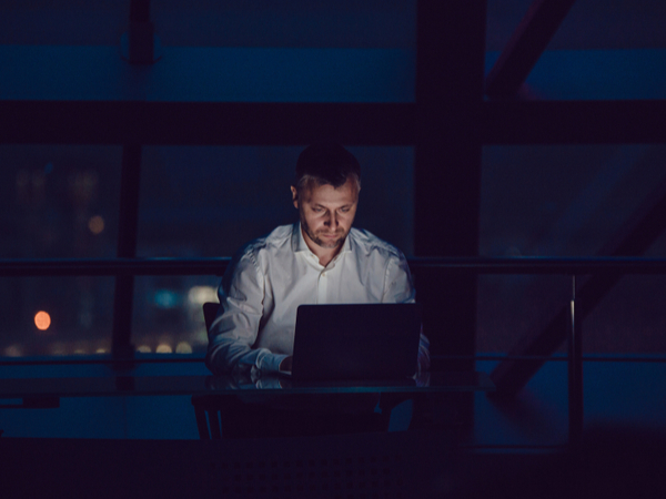 A man working alone on a laptop in the dark at home
