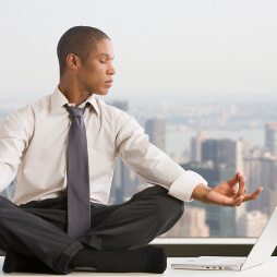 Man in a shirt and tie, in a meditating pose, looking at laptop to his side