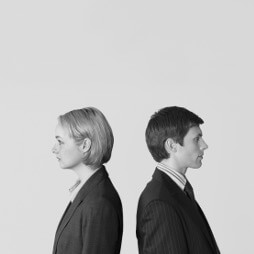 Man and woman, wearing suits, standing back to back, only top half visible