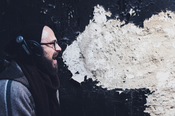 Man against wall with chipped paint in shape of speech bubble