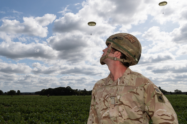 A soldier watching parachutes come down
