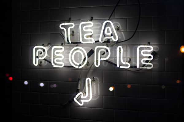 A neon sign with an arrow and the words Tea People