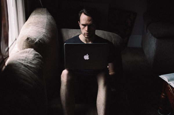 A sad looking man sat on an arm chair in the dark working at a laptop