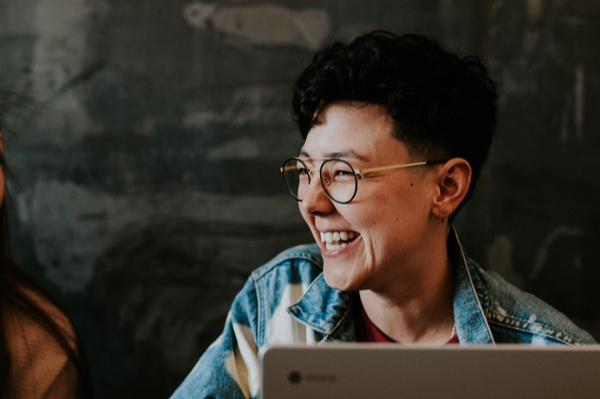 Woman laughing infront of laptop