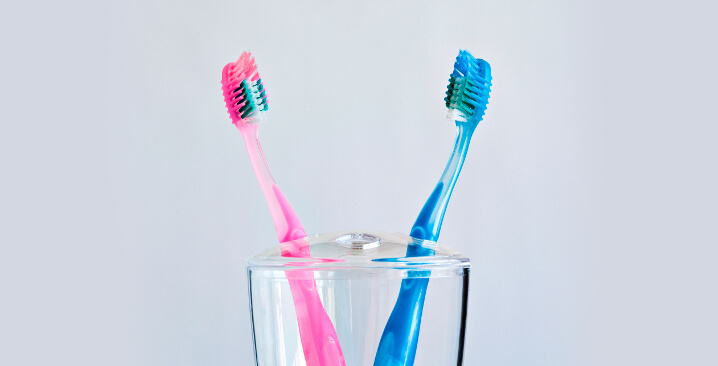 Photo of two tooth brushes, one pink, one blue, in a glass on a light grey background