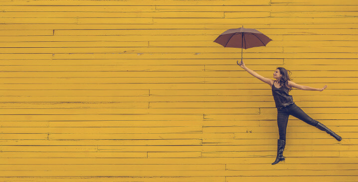 Photo of a woman jumping with an umbrella in front of a yellow brick wall