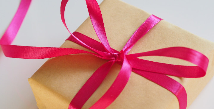Photo of a small present, wrapped in yellow plain paper and a pink ribbon tidied into a bow